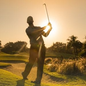 Sunset behind a man golfing at Boca West Country Club