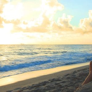 Woman sitting on a beach at sunrise in South Florida