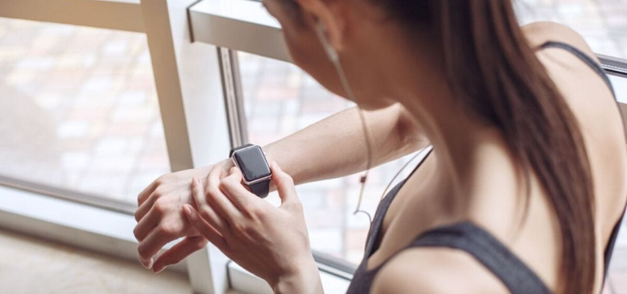 Woman Looking Down at Her Watch Getting Ready to Work Out